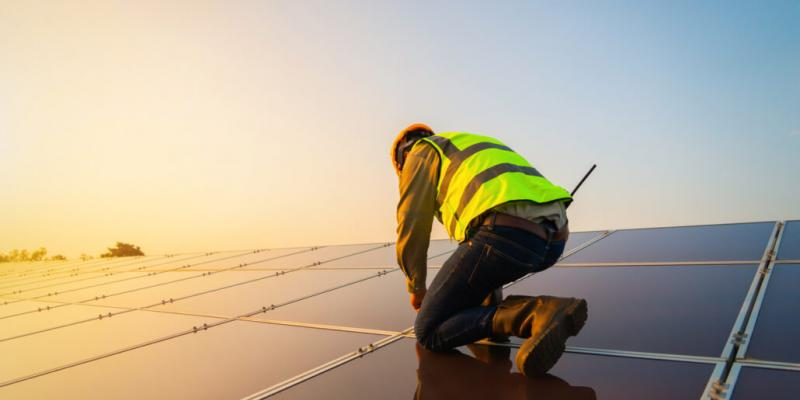 Image of a technician working on panels at a solar farm